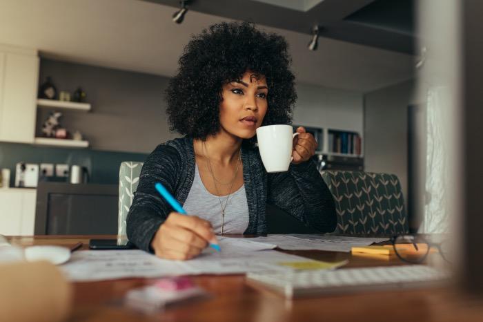 Frau im Home-office mit Kaffe in der hand