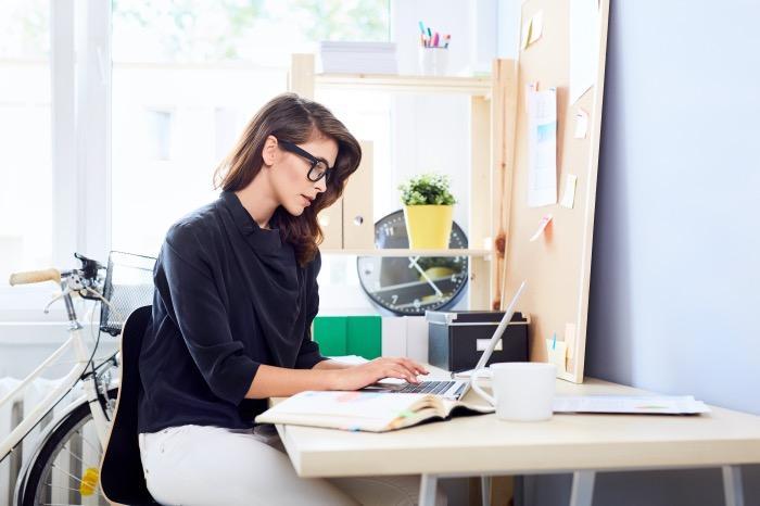 konzentrierte junge Frau sitzt am computer