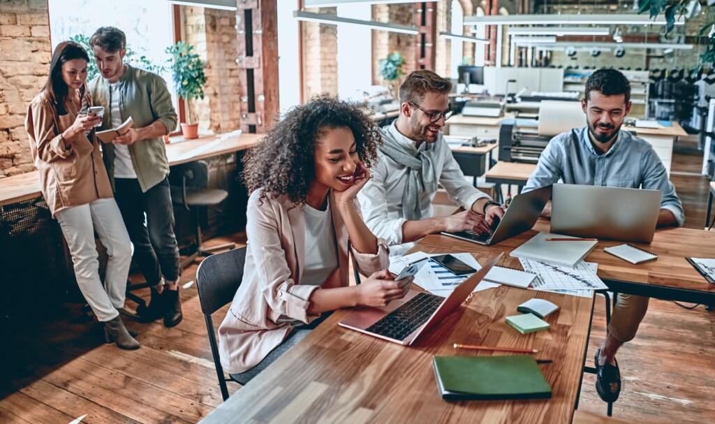 Gruppe von jungen multikulturellen Geschäftsleuten arbeiten in einem modernen Büro. Freiberufler in Coworking Ort. Kreative und stilvolle Jugend.